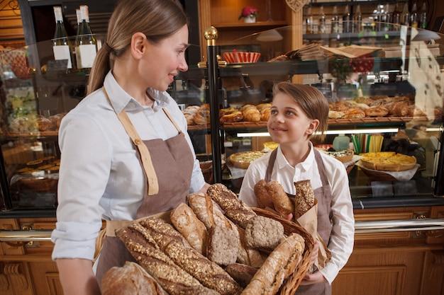 Charmanter kleiner junge und seine mutter professioneller bäcker, der köstliches brot in ihrer familienbäckerei verkauft