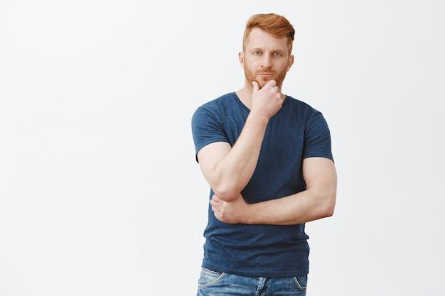 Charmanter männlicher rothaariger mann im blauen t-shirt, der bart berührt und mit nachdenklichem blick blickt, denkt, entscheidung oder wahl über graue wand trifft, interessante idee im sinn hat