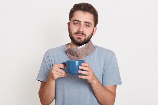 Charmanter magnetischer hübscher junger bärtiger mann, der tasse mit tee am morgen hält und friedlichen gesichtsausdruck hat
