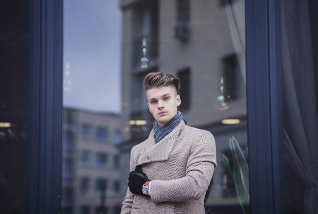 Charmanter mann. hübscher junger mann im mantel in der stadt