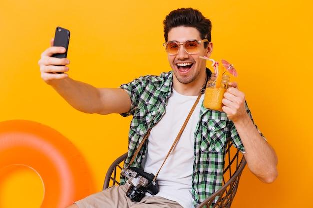 Charmanter mann im karierten hemd hält orange cocktail und nimmt selfie. kerl in der sonnenbrille wirft mit retro-kamera auf isoliertem raum mit aufblasbarem kreis auf.