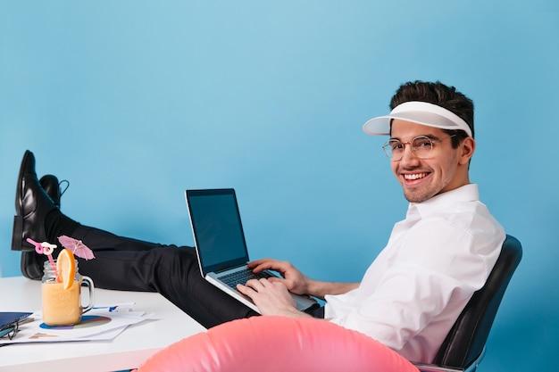 Charmanter mann in weißem hemd, mütze und brille ist gegen blauen raum. guy hält laptop und arbeitet im urlaub.