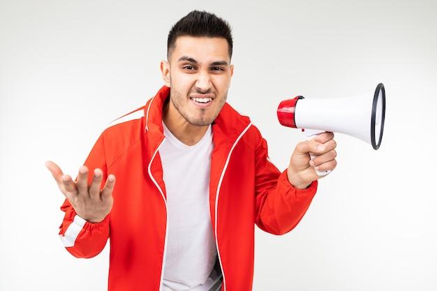 Charmanter mann mit einem megaphon in den händen ruft die nachrichten über rabatte für einkäufe auf einem weißen