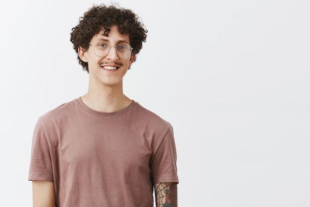 Charmanter motivierter, gut aussehender, lockiger typ mit schnurrbart und tätowiertem arm in brille und trendigem t-shirt, der freudig lächelt und sich freundlich fühlt, wenn er träume erfüllt