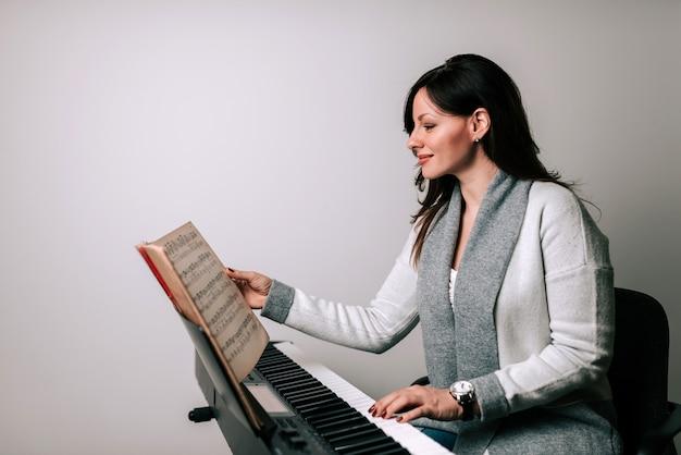 Charmanter musiker, der das klassische klavierspielen von den noten aus übt