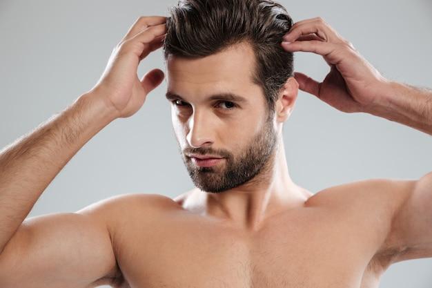 Charmanter nackter bärtiger mann, der seine haare aufwirft und berührt