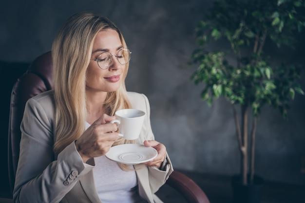 Charmanter süßer ceo, der eine tasse kaffee in einer brille genießt, die ruhe hat