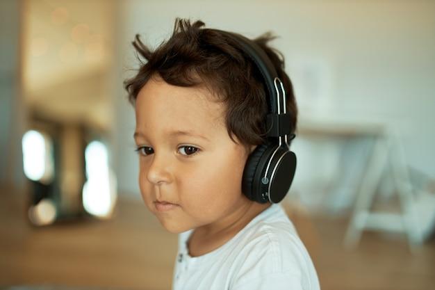 Charmanter süßer kleiner junge mit lockigem haar drinnen mit kabellosem headset