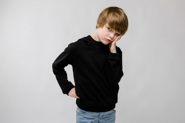 Charmanter teenager mit blonden haaren und dunklen augen. der teenager stützte seine wange mit den fingern ab. der teenager ist unzufrieden