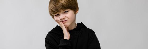 Charmanter teenager mit blonden haaren und dunklen augen.