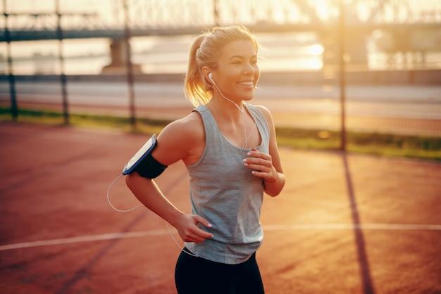 Charmanter weiblicher blonder läufer in der sportbekleidung, die auf hof mit kopfhörern in den ohren und smartphone in der telefonhülle um arm läuft.