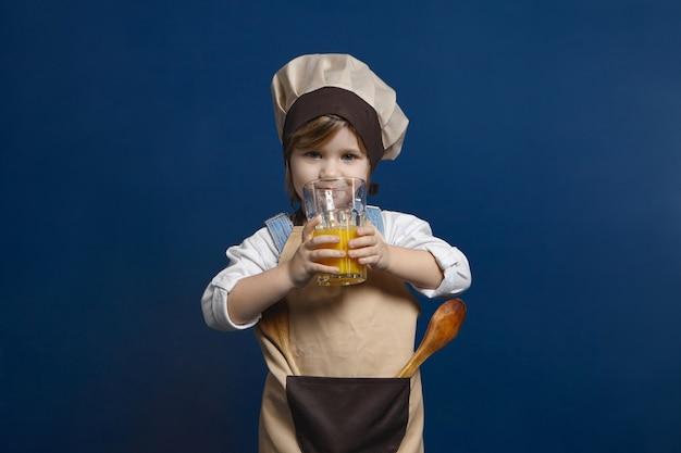 Charmantes 5 jahre altes baby, das styling-schürze und kochmütze trägt, die mit utensilien aufwirft