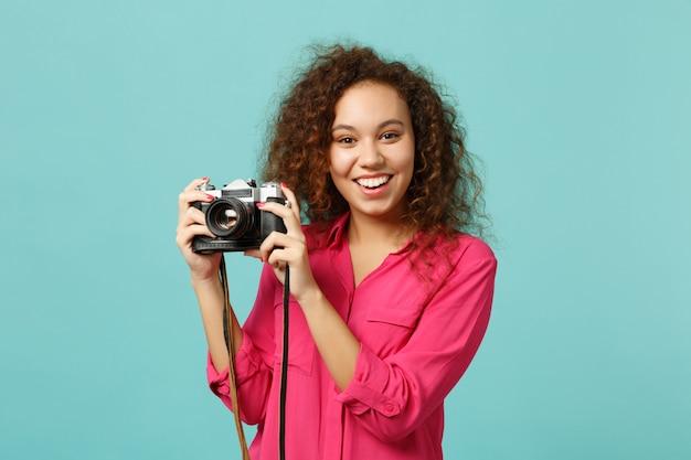 Charmantes afrikanisches mädchen in freizeitkleidung, das ein foto auf einer retro-vintage-fotokamera macht, die auf blau-türkisem wandhintergrund im studio isoliert ist. menschen aufrichtiges emotions-lifestyle-konzept. kopieren sie platz.