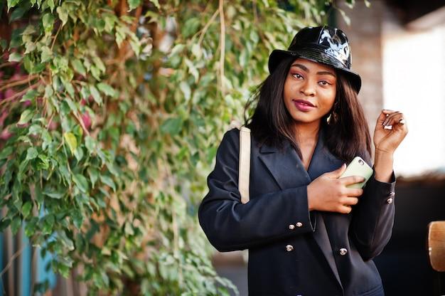 Charmantes afroamerikanisches frauenmodell in der schwarzen jacke, im hut und in der hüfttasche, die im café während der freizeit mit handy entspannen.