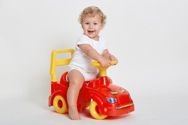 Charmantes baby, das auf rotem und gelbem tolocar sitzt und weißen körperanzug trägt