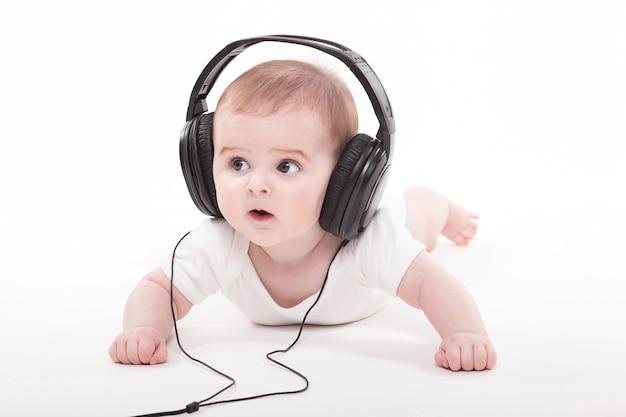 Charmantes baby mit kopfhörern zu hören