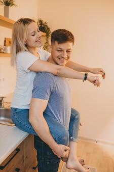 Charmantes blondes mädchen, das ihren geliebten umarmt, während es in der küche sitzt und zeit zusammen verbringt
