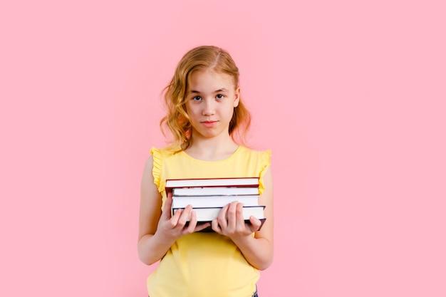 Charmantes blondes mädchen im gelben t-shirt, das mit übungsbüchern aufwirft Premium Fotos