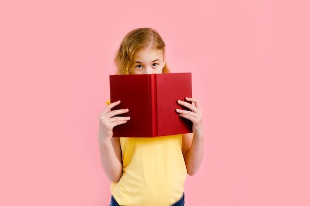 Charmantes blondes mädchen im gelben t-shirt, das mit übungsbüchern aufwirft