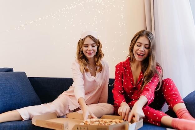 Charmantes blondes mädchen in der rosa nachtwäsche, die pizza mit bester freundin isst und lächelt. zwei fröhliche damen, die beim frühstück zu hause fast food genießen.