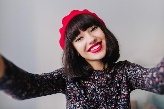 Charmantes brünettes mädchen mit hellem make-up breit lächelnd, während selfie in ihrem zimmer machen. nahaufnahmeporträt der entzückenden jungen dunkelhaarigen frau, die niedliches weinlese-outfit und rote französische baskenmütze trägt