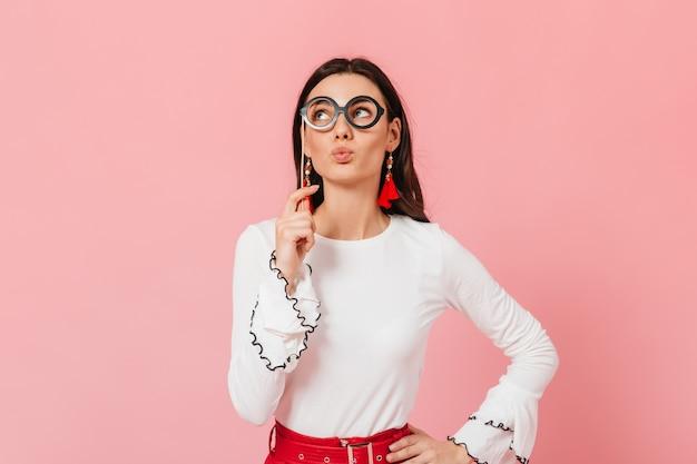 Charmantes dunkelhaariges mädchen in schwarzer brille faltete die lippen zum kuss. foto der dame in der weißen bluse und in den roten ohrringen.
