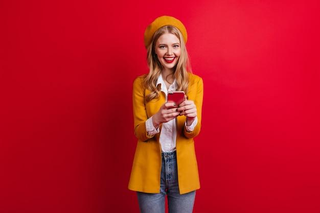 Charmantes französisches mädchen mit telefon an der roten wand. lachende blonde frau in der gelben jacke, die smartphone hält.