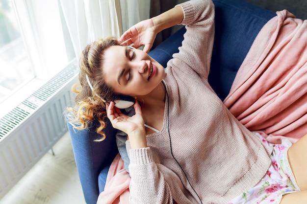 Charmantes glückliches mädchen mit blonder gewellter frisur, die auf blauem sofa auf ihrem wohnzimmer liegt und nach oben schaut. nettes mädchen, das zeichen zeigt, die lieblingsmusik genießen.
