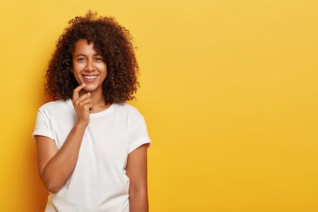 Charmantes, gut aussehendes junges mädchen mit afro-haaren, lächelt sanft, hat natürliche schönheit, ist in hochstimmung, genießt eine tolle zeit am wochenende und trägt weiße freizeitkleidung, die auf gelb isoliert ist