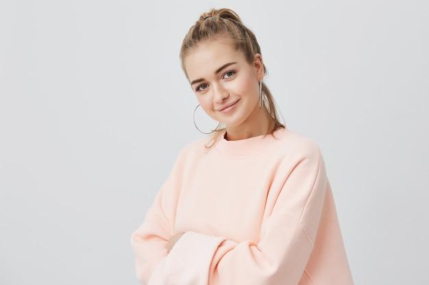 Charmantes, gut aussehendes, stilvolles europäisches mädchen, das mit ihren dunklen augen sitzt, lächelt und ein rosa sweatshirt mit großen runden ohrringen trägt. schönheits- und jugendkonzept.