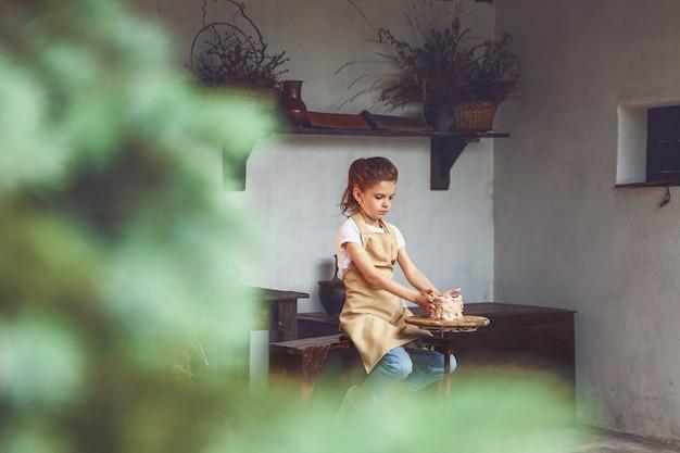 Charmantes handwerkliches kleines mädchen, das keramikkunst und produktionsprozess genießt