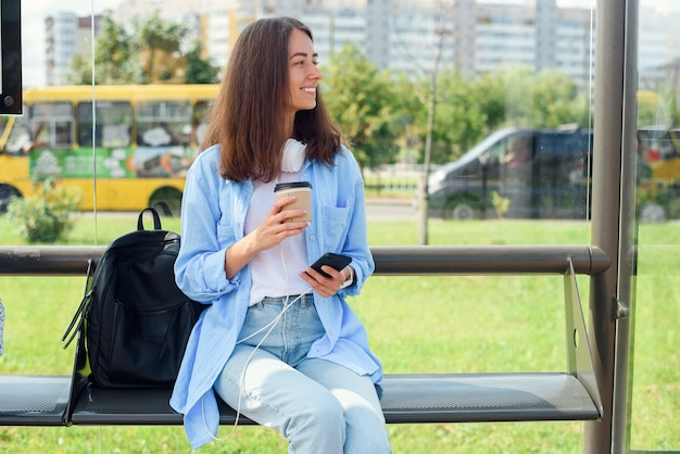 Charmantes hipster-mädchen, das am morgen mit einer tasse kaffee auf bus oder straßenbahn auf der station des öffentlichen verkehrs wartet