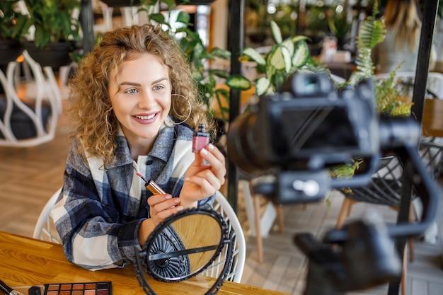 Charmantes junges mädchen, das ihre video-blog-episode über neue kosmetische lippenstiftprodukte aufzeichnet, während sie zu hause am tisch sitzt und sich schminkt