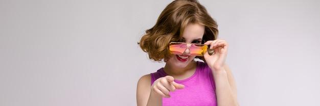 Charmantes junges mädchen im rosa kleid. fröhliches mädchen in quadratischen gläsern.