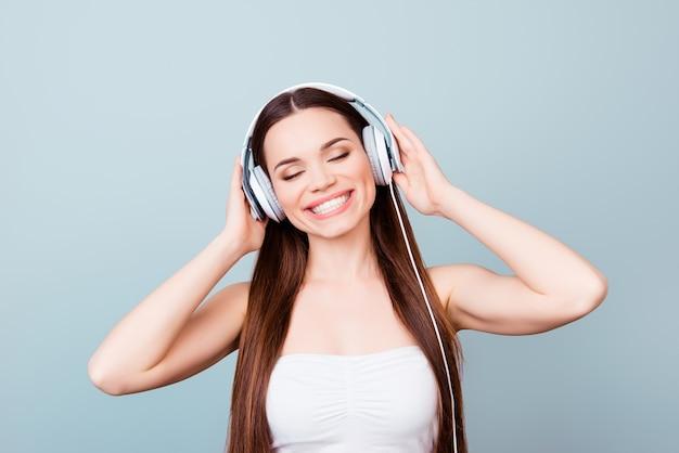 Charmantes junges mädchen mit zahnigem lächeln in modernen kopfhörern. sie ist verträumt und glücklich, hört ihr lieblingslied, hält die kopfhörer in der hand, mit geschlossenen augen auf den reinen raum