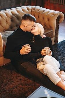 Charmantes junges paar, das sich auf dem boden umarmt und sich auf eine couch stützt, während es lächelt, bevor es küsst