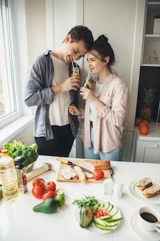 Charmantes kaukasisches paar, das einen mojito zusammen trinkt, während essen in der küche zubereitet
