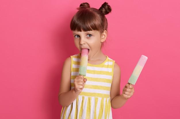 Charmantes kind beißt fruchtwassereis. glück und freude des kleinen mädchens, das sommer trägt, freie und leichte sommertage verbringt.