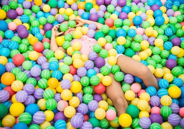 Charmantes kind, das im pool mit hellen bunten plastikbällen liegt. mädchen gekleidet in rosa bluse und weißen shorts