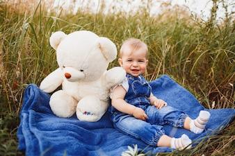 Charmantes kleines Mädchen sitzt mit einem großen Spielzeug weißen Bären auf dem Feld