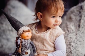 Charmantes kleines Mädchen spielt mit einer Puppe