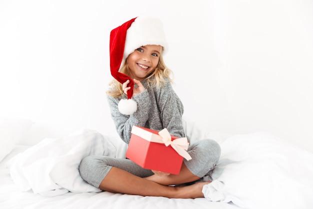Charmantes kleines mädchen, das den hut ihres weihnachtsmanns berührt, der geschenkbox hält, während auf bett sitzt