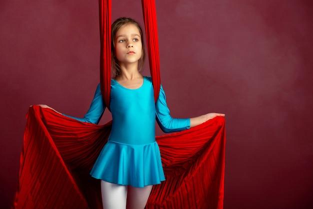 Charmantes kleines mädchen in einem blauen turnanzug, der für leistung mit einem roten luftigen band auf einem rot-blassen hintergrund vorbereitet wird. konzept sport kinderakrobatik. platz für werbung