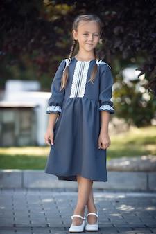 Charmantes kleines mädchen in einem retro-kleid, das an einem sonnigen sommertag in der stadt spaziert. kleines mädchen trägt schuluniform. grundschulmädchen mit langen haaren. studium und ausbildung.