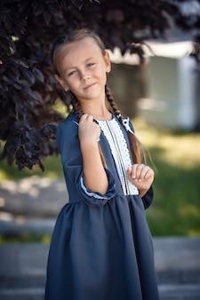 Charmantes kleines mädchen in einem retro-kleid, das in der stadt an einem sonnigen sommertag geht. kleines mädchen tragen schuluniform. Premium Fotos