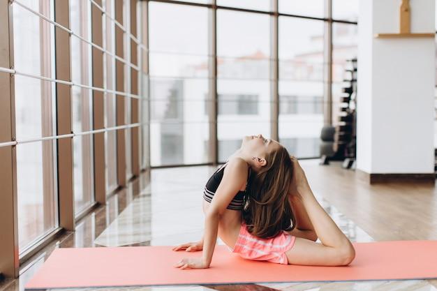 Charmantes kleines mädchen lächelt, während es yoga in der fitnesshalle macht