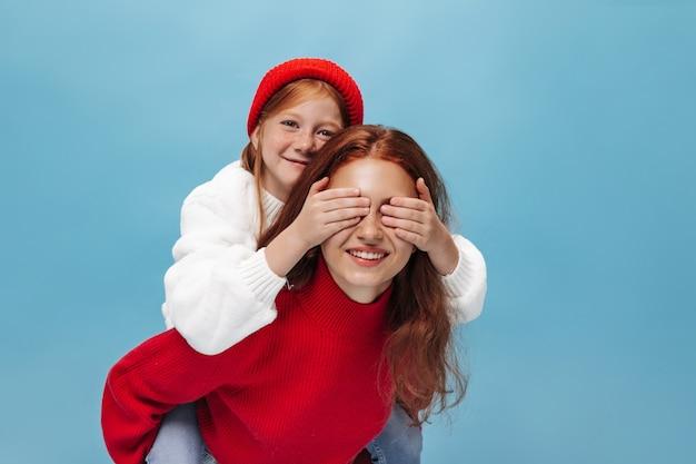 Charmantes kleines mädchen mit ingwerhaar in roter mütze und weißem pullover schließt die augen ihrer lächelnden älteren schwester in hellen kleidern