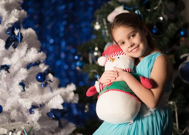 Charmantes kleines mädchen mit pinocchio schmückt einen weihnachtsbaum
