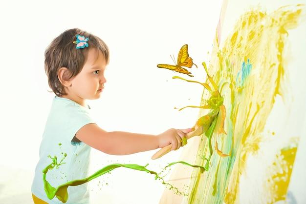 Charmantes kleines zweijähriges kind zeichnet mit einem pinsel eine magische fantasiezeichnung, die durch berührung zum leben erwacht. das konzept der kreativität von kindern, freundlichkeit und fantasie