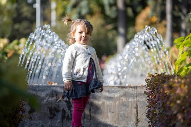 Charmantes kleinkind im park mit springbrunnen im hintergrund. sommertag